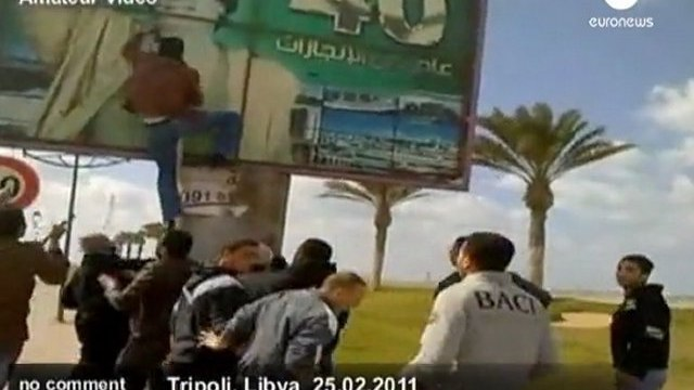 Protesters tearing down Gaddafi's billboard - no comment
