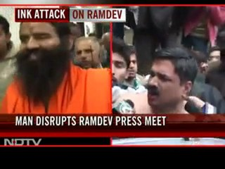 Man throws black ink at Baba Ramdev during a press conference in Delhi
