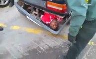 Homme caché dans le pare-choc d'une voiture