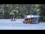 Motor boat and traditional race boat sailing on backwaters of Kerala