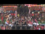 Hindu priests sit on the chariot as devotees pull chariot
