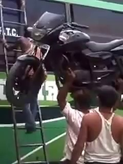 Indian Guy puts motorcycle on roof of a bus with his head