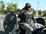 Guy Bench Presses Weights While Riding a Motorcycle Wheelie