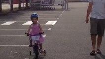 Jeanne fait du vélo avec les roulettes