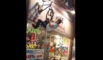 Un homme ivre s'accroche a l'enseigne d'un magasin de vélo