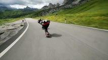 Skateboarders doublent des cyclistes dans une descente des Alpes