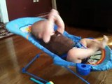 Un bébé fait des abdos sur son lit