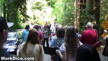 Hundreds of Bohemian Grove protesters march to the gates of the club