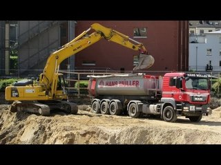KOMATSU EXCAVATOR PC240 LOADING DUMP TRUCKS ON CONSTRUCTION SITE