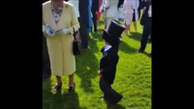 Cute boys takes off hat, shake hands with Queen Elisabeth