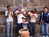 Un grupo de niños toca con gran entusiasmo por unas monedas en las calles de Quito (Ecuador)