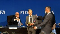 Lee Nelson showers Sepp Blatter with banknotes in prank