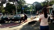 Un homme déplace une voiture garée sur une piste cyclable à mains nues