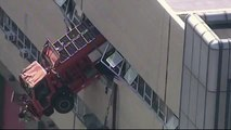 Sanitation truck dangles from building in New York
