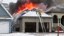 Firefighters fall off ladder at house fire.