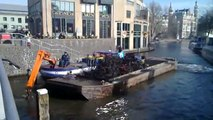 Boat crane cleaning water in Amsterdam channels from bikes