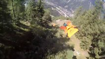 Trois wingsuiters volent à travers les arbres d'une montagne