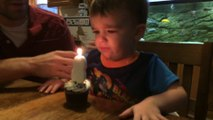 Kid has trouble blowing his birthday candle