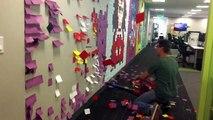 Des collègues de bureau enlève des fresque de Post-It au souffleur à feuilles