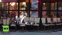 Les experts de médecine légale inspectent le corps d'un des terroristes qui s'est fait exploser devant le café Comptoir