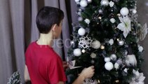 Little Boy Hangs White Toy On Decorated Xmas Tree | Stock Footage - Videohive