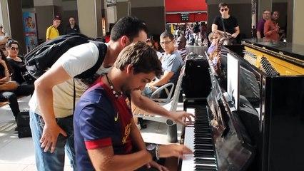 Deux jeunes hommes improvisent un morceau au piano pour le plus grand bonheur des voyageurs