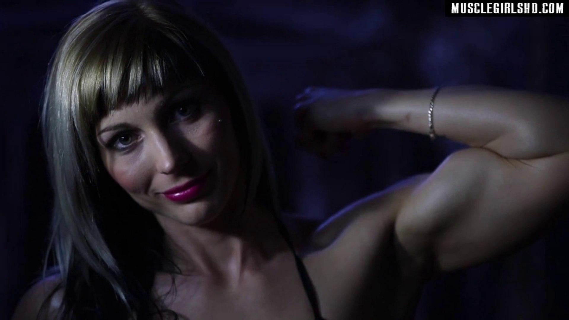 Young Female Bodybuilder Flexing Biceps