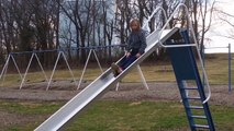 Girl Slowly Slides Down Squeaky Slide