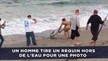 Un homme tire un requin hors de l'eau pour prendre une photo avec lui