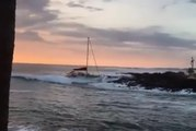 Une grosse vague envoie un catamaran dans les rochers