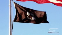 Tilting close-up shot of American and POW/MIA flags flying over Korean War Veterans Memorial
