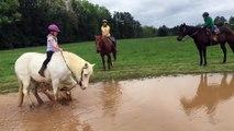 Un poney fait trempette avec une enfant sur son dos
