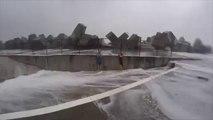Ces surfeurs se planquent deriière un mur pour se protéger d'énormes vagues