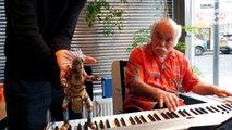 Une marionnette danse avec un pianiste qui joue dans un restaurant...