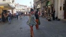 Une femme accompagne un musicien de rue en dansant