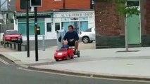 Un enfant ramène son père du pub en le conduisant avec sa voiturette