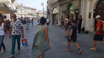 Une fille se met à danser sur la musique de musiciens de rue