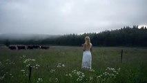 Une jolie fille appelle un troupeau de vaches