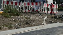 White Car Have Passed by Red and White Safety Fence Man is Walking Red Water Source With Hosepipe
