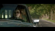 La dame dans l'auto avec des lunettes et un fusil
