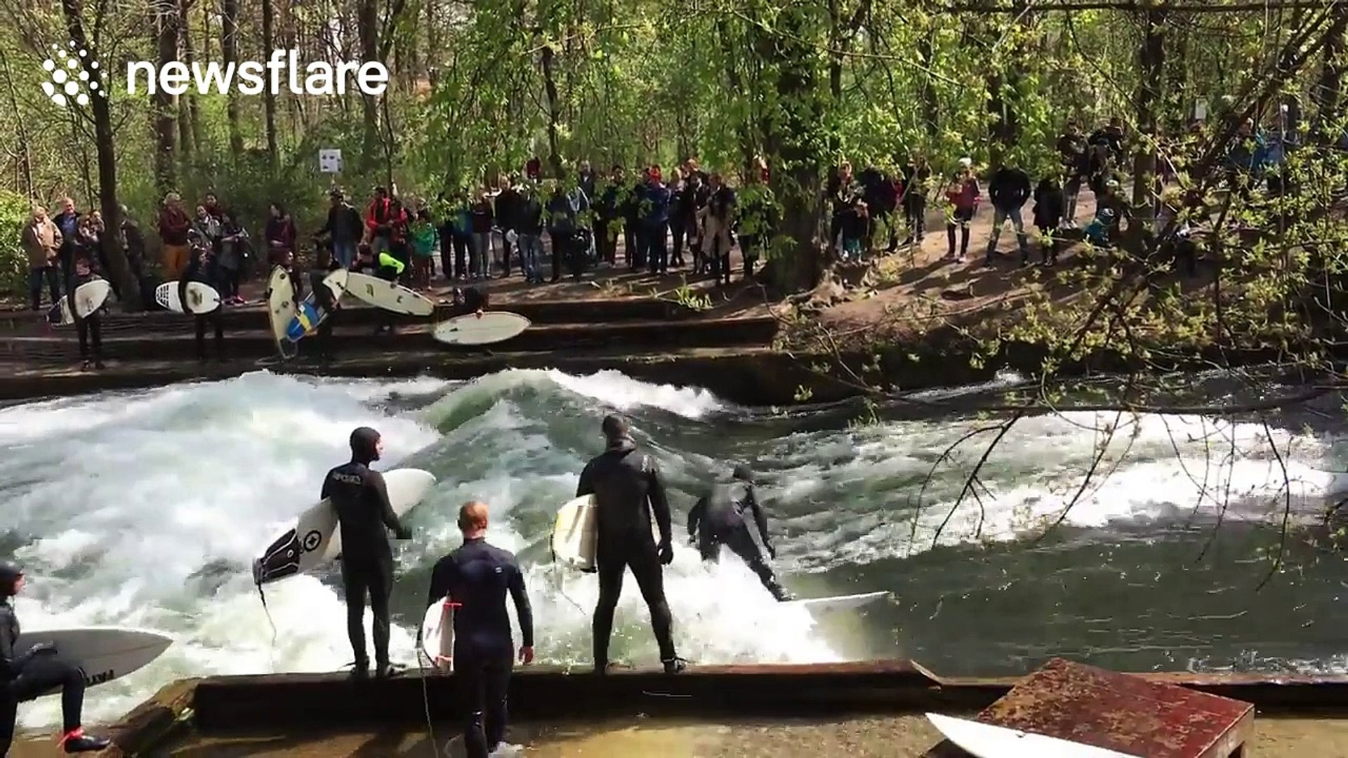 Surfers ride waves on river in Munich