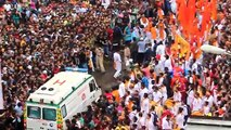 Une foule laisse passer une ambulance