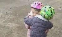 Une petite fille réconforte son copain qui vient de faire une chute à vélo.