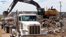 Deere 470G excavator loading debris into a double big rig dump truck on a windy day construction site