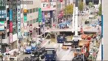 Les ouvriers Japonais refont la route effondrée la semaine précédente, détruite par un glissement de terrain
