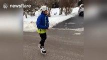 Boy ice-skates on frozen road in Ontario, Canada