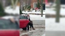 Une jeune femme se fait aider par son père pour grimper dans sa voiture stationnée dans une allée verglacée