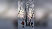 Le père tape dans cet arbre et la neige tombe sur ses enfants