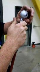 Il fait la toupie dans sa main avec une balle de golf avec un compresseur à air