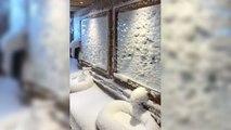 La neige s'infiltre par une fenêtre ouverte dans un restaurant